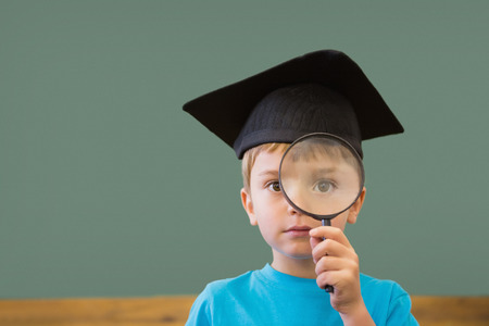schoolkid search: Cute pupil in mortar board smiling at camera in classroom at the elementary school Stock Photo
