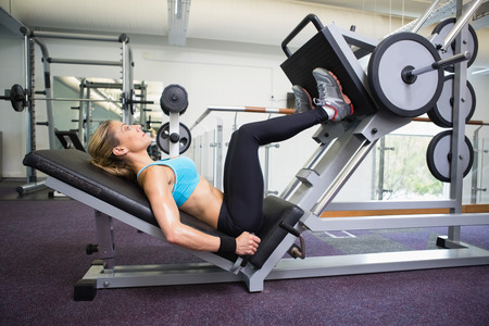 body toning: Side view of a fit young woman doing leg presses in the gym