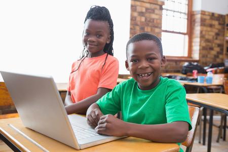 niños negros: Alumnos lindo usando la computadora portátil en el aula en la escuela primaria Foto de archivo
