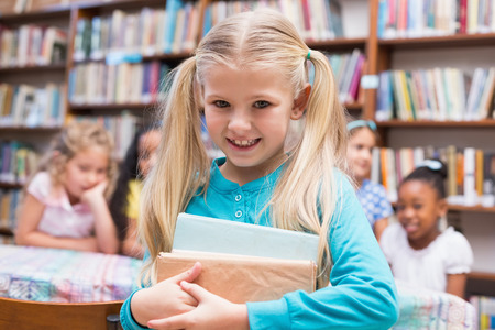 Cute pupils looking at camera in library at the elementary school photo