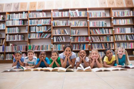 Mignon élèves et enseignants se trouvant sur le sol dans la bibliothèque à l'école primaire
