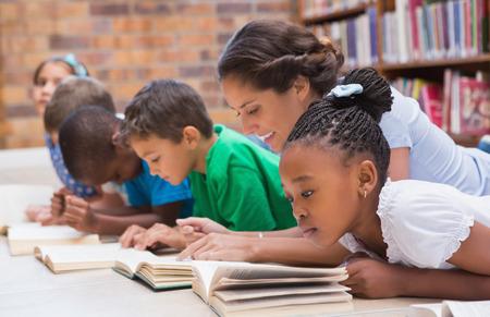 かわいい生徒と教師、小学校の図書館で床に横たわって