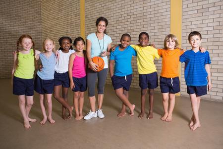 girl sport: Carino alunni che sorride alla macchina fotografica con insegnante di educazione fisica presso la scuola elementare