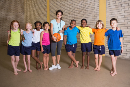 sport team: Cute pupils smiling at camera with PE teacher at the elementary school Stock Photo
