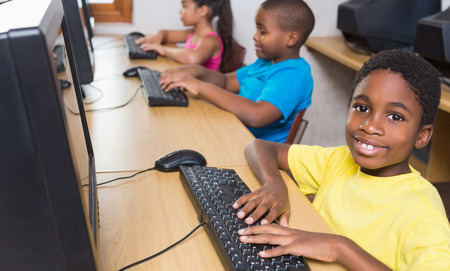 Cute pupils in computer class at the elementary school photo