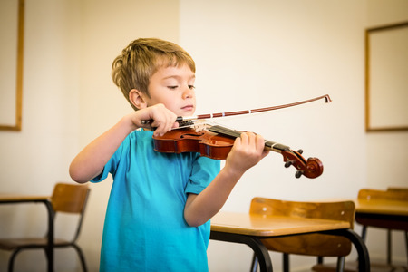 Cute pupil playing violin in classroom at the elementary school photo
