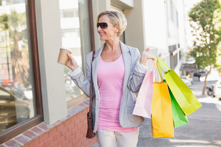 fair woman: Happy mature woman walking with her shopping purchases on a sunny day