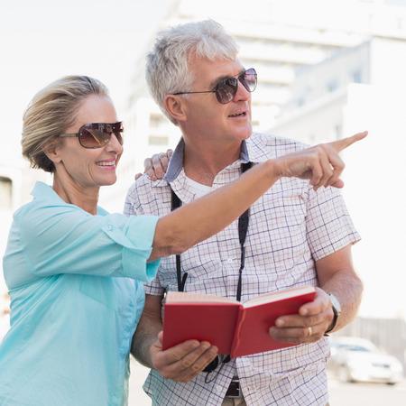 guia turistico: Pareja de turistas felices usando el libro gu�a de turismo en la ciudad en un d�a soleado