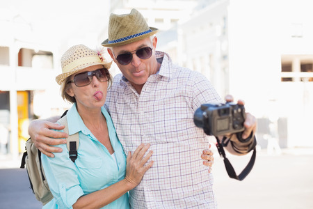 Happy tourist couple taking a selfie in the city on a sunny day photo