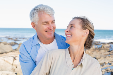Happy casual couple hugging by the coast on a sunny day photo