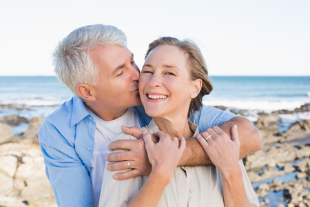 Happy casual couple by the coast on a sunny day photo