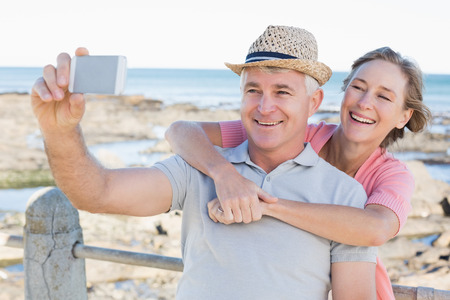 Happy casual couple taking a selfie by the coast on a sunny day photo