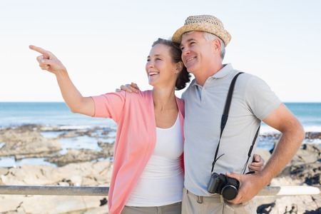 Happy casual couple looking at something by the coast on a sunny day photo