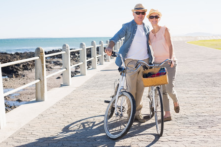 Happy casual couple going for a bike ride on the pier on a sunny day photo