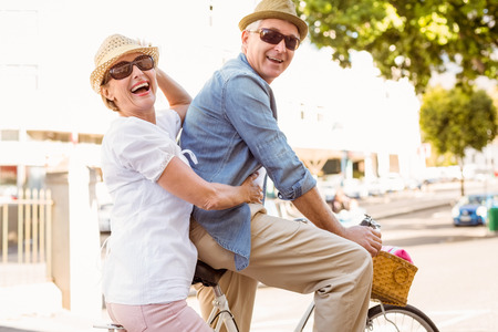 bike riding: Happy mature couple going for a bike ride in the city on a sunny day