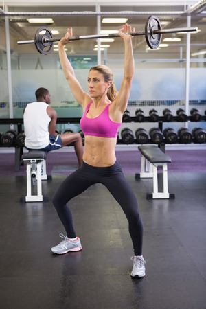 Full length of a fit young woman lifting barbell in the gym photo