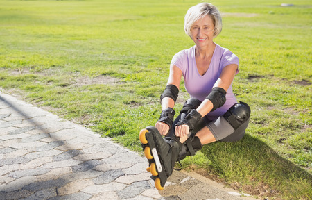 elbow pads: Active senior woman ready to go rollerblading on a sunny day Stock Photo