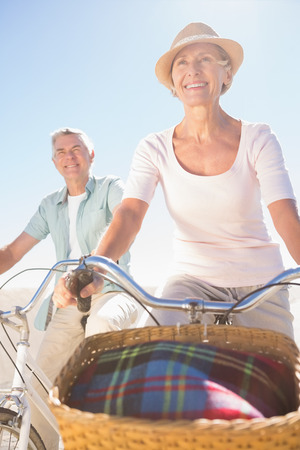 Happy senior couple going for a bike ride on a sunny day