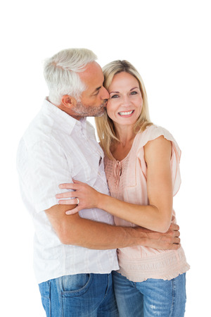 Affectionate man kissing his wife on the cheek on white background photo