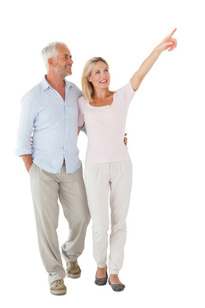 Smiling couple walking and pointing on white background