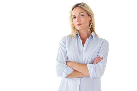unsmiling: Serious blonde posing with arms crossed on white background Stock Photo