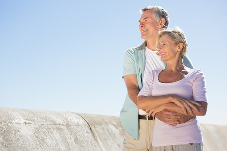 chinos: Happy senior couple embracing on the pier on a sunny day