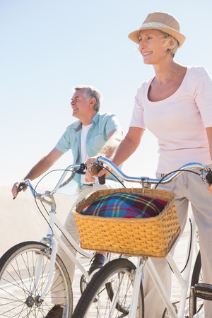 Happy senior couple going for a bike ride on a sunny day photo