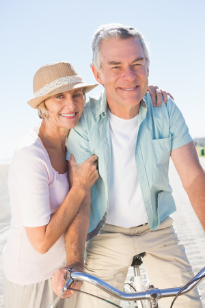 chinos: Happy senior couple going for a bike ride on a sunny day