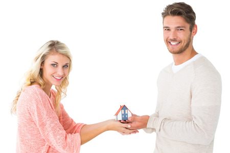 Attractive couple holding miniature house model on white background photo