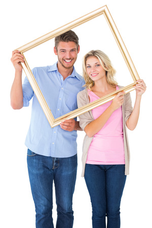 Attractive young couple holding picture frame on white background