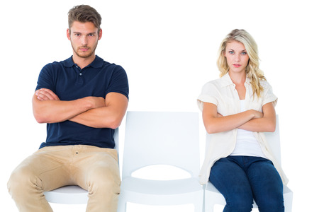 not talking: Young couple sitting in chairs not talking during argument on white background