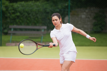 Tennis player playing on the court on a sunny day photo