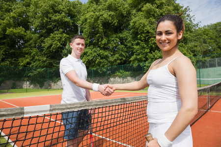 opponents: Tennis opponents shaking hands before match on a sunny day
