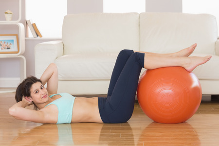 Fit brunette doing sit ups with exercise ball at home in the living room photo