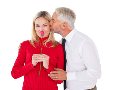 Handsome man giving his wife a kiss on cheek on white background photo