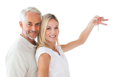 Happy couple showing their new house key on white background photo
