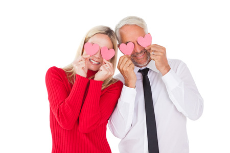 ttractive: Silly couple holding hearts over their eyes on white background Stock Photo