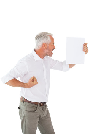 outraged: Angry man shouting at piece of paper on white background