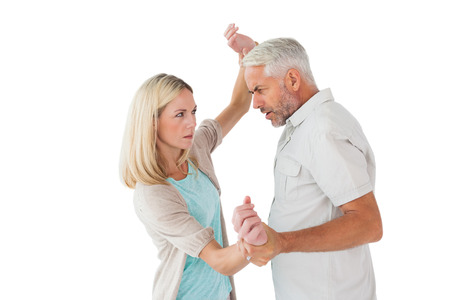 overpowering: Angry man overpowering his partner on white background