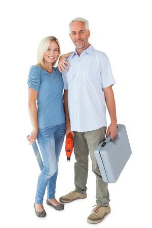 Happy couple holding DIY tools on white background photo