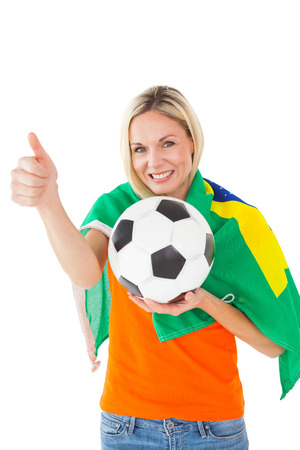 Football fan holding ball and wearing brazil flag on white background photo