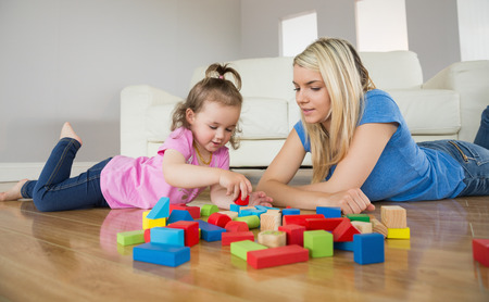 apartment blocks: Relaxed mother and daughter playing with building blocks on wooden floor at home Stock Photo