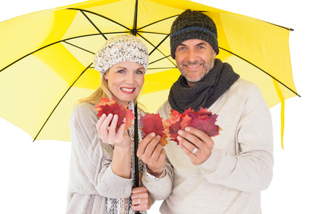 Couple in winter fashion showing autumn leaves under umbrella on white background photo