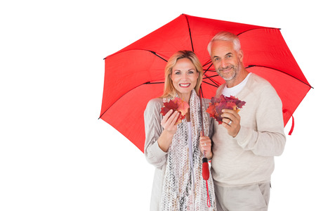 Smiling couple showing autumn leaves under umbrella on white background photo