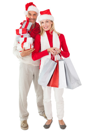 Festive couple holding presents and shopping bags on white background photo