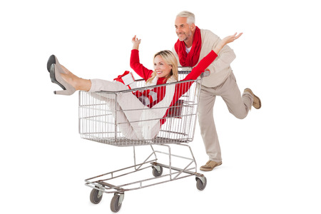boodschappenkar: Festive couple messing about in shopping trolley on white background Stockfoto