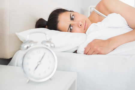 bedside table: Beautiful young woman looking at alarm clock on bedside table at home