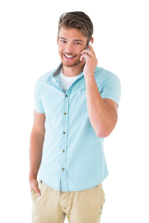 chinos: Handsome young man talking on his smartphone on white background