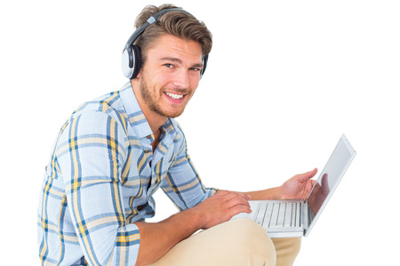 chinos: Handsome young man sitting using laptop on white background