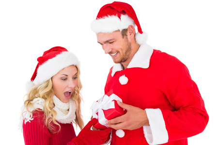 Festive young couple exchanging presents on white background photo